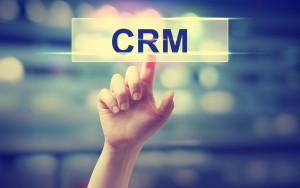 CRM - Customer Relationship Management concept with hand pressing a button on blurred abstract background